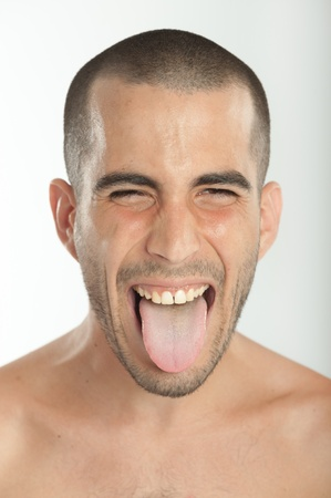 shirtless man: Portrait of a young man sticking his tongue out