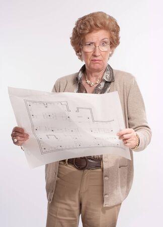 Portrait of a displeased senior lady holding architecture blueprints  photo