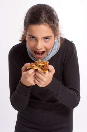 early teens:  Portrait of a girl in her early teens eating a pizza part with relish  Stock Photo