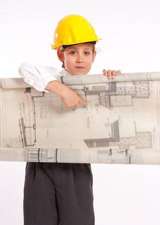 safety helmet: Muchacho joven que llevaba un casco de seguridad, la celebraci�n de planos de arquitectura Foto de archivo