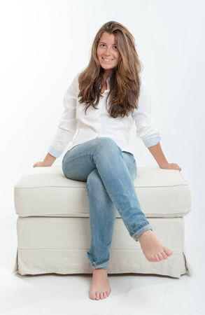 the stool: Pretty young brunette sitting on a stool Stock Photo