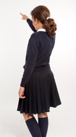 schoolgirl uniform:  Rear view of  a schoolgirl pointing at something, isolated in white