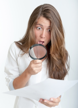 Young woman with a shocked expression examining a document with a magnifying glass Stock Photo - 16306095