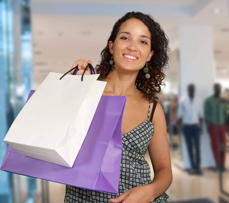 materialism: Happy exotic woman shopping at the mall