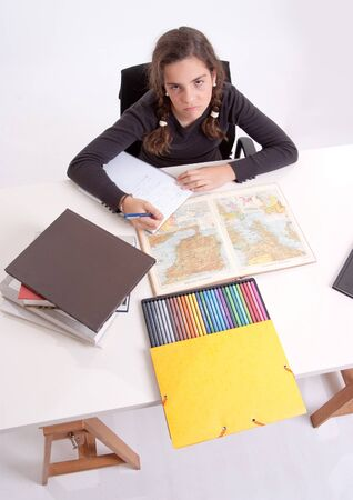 Young girl with a fed-up expression doing schoolwork Stock Photo - 16467125
