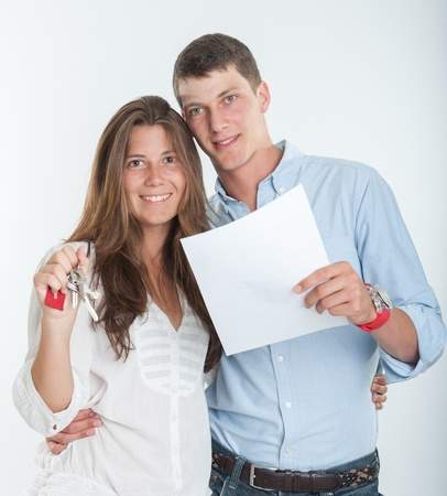 dream house: Young couple holding a document and a bunch of keys