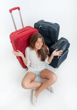 Happy young woman sitting on the floor surrounded by luggage Stock Photo - 16467085