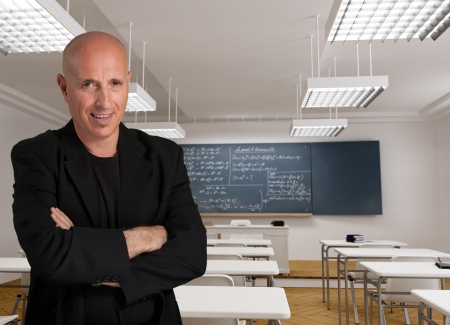 formulae:  Bald man in a black suit in a classroom with mathematic formulae  Stock Photo