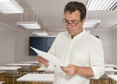 formulae: Serious teacher in a classroom, reading a paper
