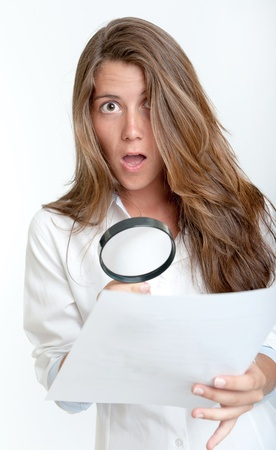 Young woman with a shocked expression examining a document with a magnifying glass photo