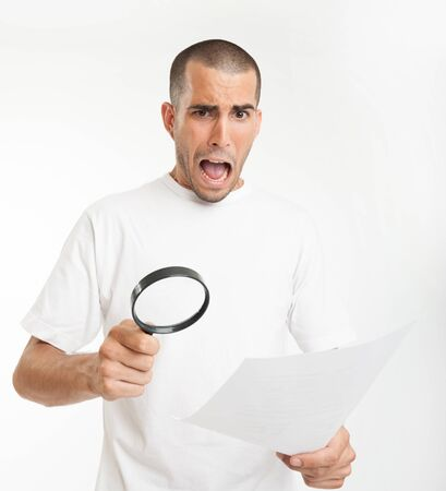 Young man reading a document through a magnifying glass with a shocked expression Stock Photo - 16467147