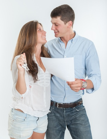 Young couple holding a document and a bunch of keys photo