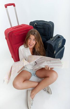 Happy young woman sitting on the floor surrounded by luggage, holding a map Stock Photo - 16546243