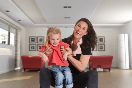 Cheerful mother holding a cute blonde little girl in a living room Stock Photo - 16546306