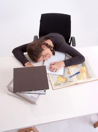 Extremely tired schoolgirl sleeping on her schoolwork Stock Photo - 16546314