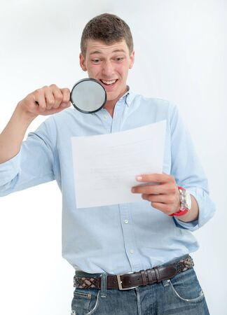 Young man with shocked expression examining a document through a magnifying lens Stock Photo - 16546252