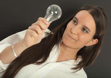pelo castaño claro: Mujer que sostiene una bombilla con una expresión de duda Foto de archivo