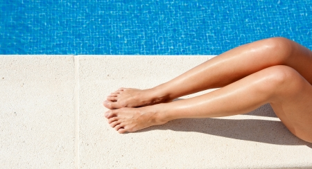 Female legs by the swimming pool   photo