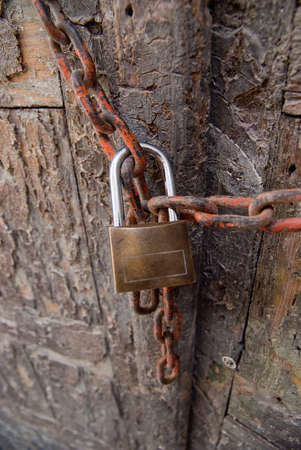 splintered: Old door locked with a rusty chain and padlock