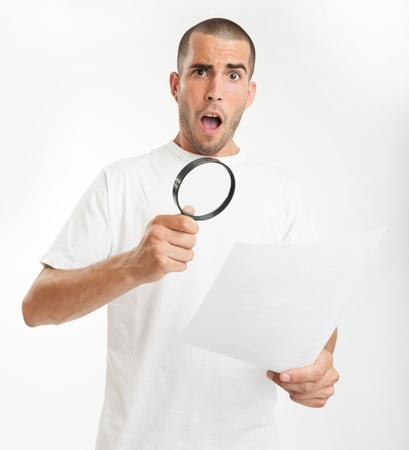 Young man reading a document through a magnifying glass with a shocked expression Stock Photo - 16657629