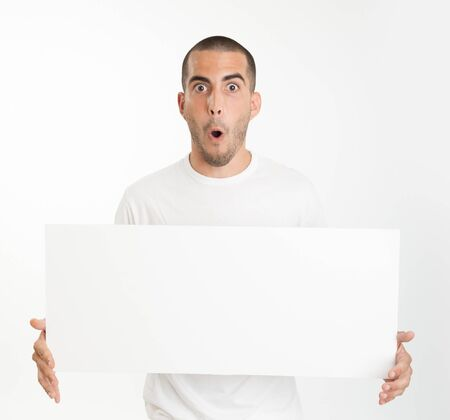 Expressive young man holding a blank board ideal for inserting your own message Stock Photo - 16657623