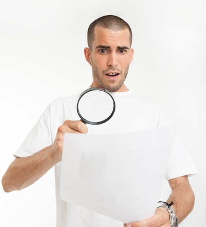 Young man reading a document through a magnifying glass with a shocked expression Stock Photo - 16951668