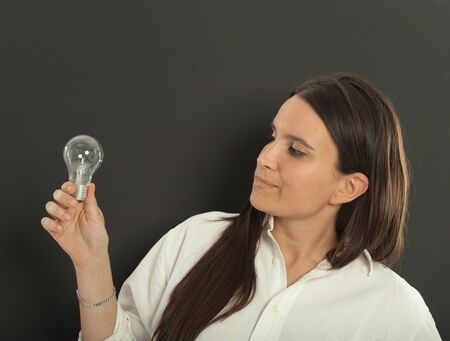 Woman holding a light bulb with a doubtful expression photo