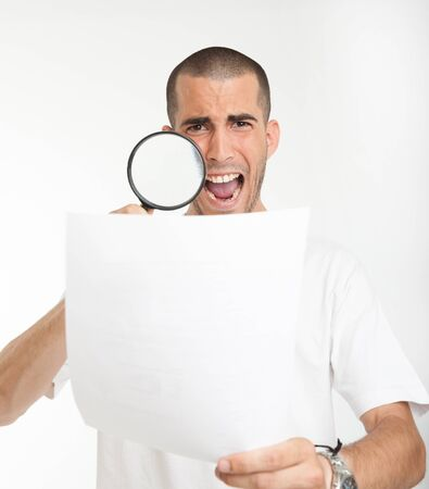 Young man reading a document through a magnifying glass with a shocked expression Stock Photo - 17417494