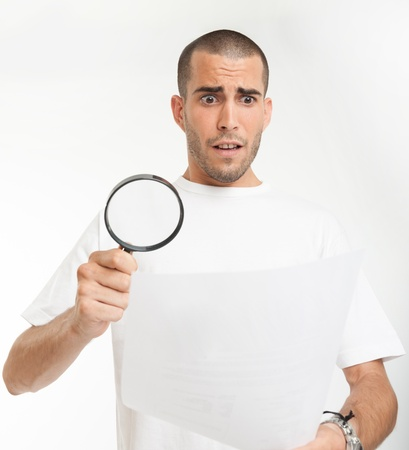 Young man reading a document through a magnifying glass with a shocked expression Stock Photo - 17417506