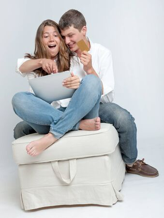 barefoot teens: Young couple sitting together with a tablet pc and a credit card