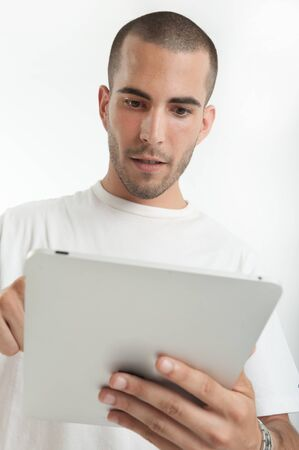 Serious looking young man with a digital tablet Stock Photo - 17572762
