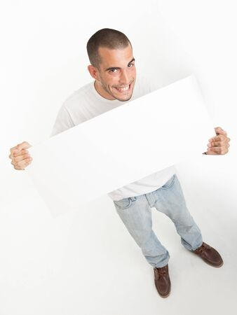Expressive young man holding a blank board ideal for inserting your own message Stock Photo - 17572727