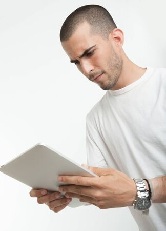 Serious looking young man with a digital tablet Stock Photo - 17601048