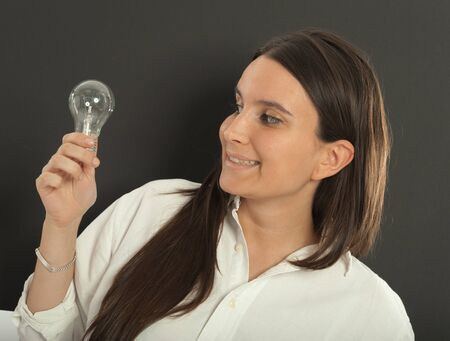 Woman holding a light bulb with a happy expression Stock Photo - 17600906