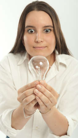 Woman holding a light bulb with a happy expression photo