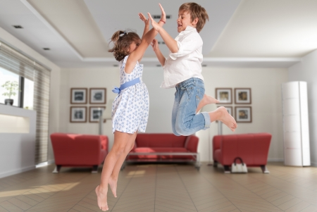 living room interior:   Little boy and girl happily jumping on a home interior