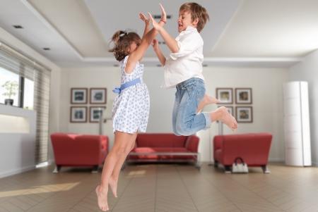 persona saltando: Ni�o y ni�a saltando alegremente en una casa interior
