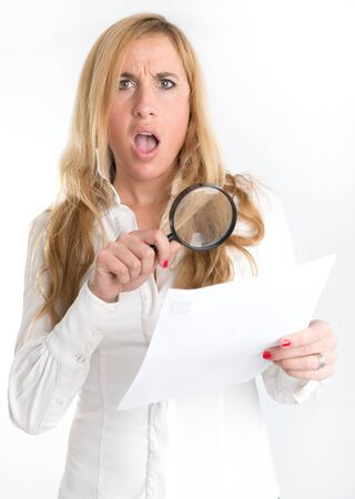 unfair: Woman with shocked expression examining a document through a magnifying glass
