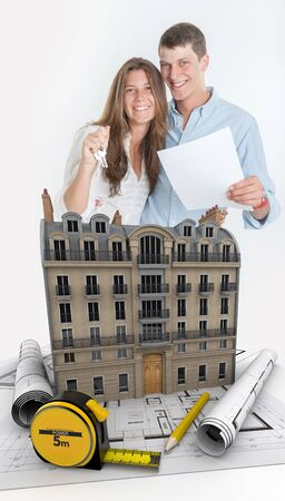 construction plans: Young couple happily holding a contract and a bunch of keys with a building and blueprints