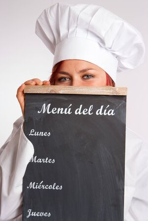 Portrait of a professional female chef holding a menu slate  photo