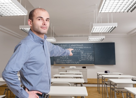 formulae:  Teacher pointing at a blackboard with mathematical formulae  Stock Photo