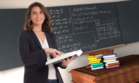 female teacher:  Cheerful female teacher holding a book in a maths classroom   Stock Photo