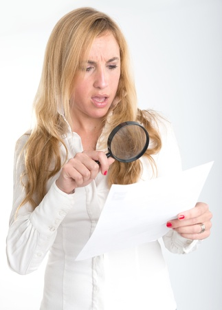 Woman with shocked expression examining a document through a magnifying glass Stock Photo - 18091718
