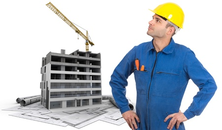 A construction worker, a building in construction and blueprints photo