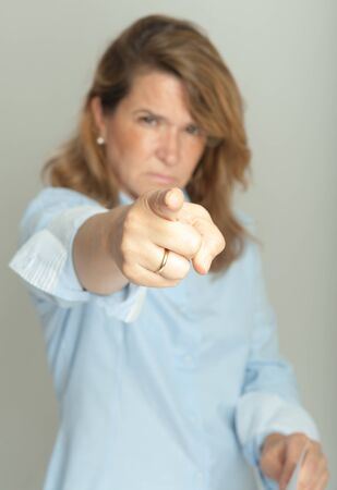 Woman with severe expression, holding a document and pointing at the camera Stock Photo