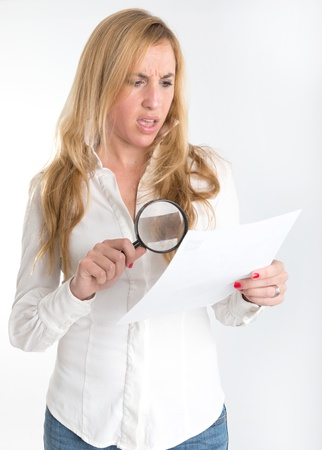 outrage: Woman with shocked expression examining a document through a magnifying glass