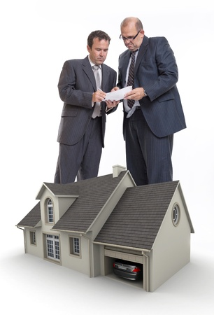 foreclosure: Two men signing a document and a house rendering Stock Photo