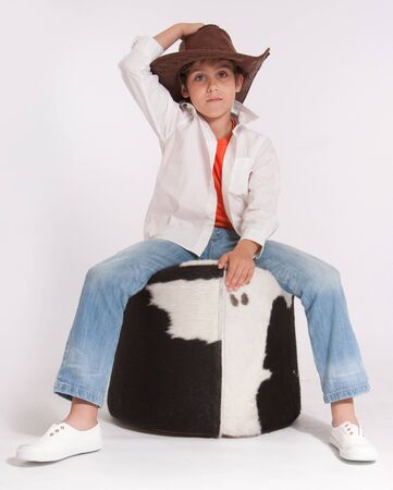 footstool:   Kid with a cowboy hat riding a cowhide footstool