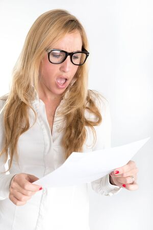 unfair: Woman with shocked expression examining a document through her reading glasses Stock Photo