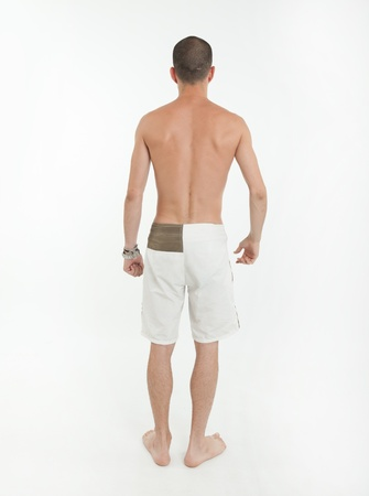 shirtless guy: Rear view of a young man wearing swimming trunks